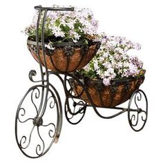 """Two-tier metal tricycle planter with a coconut fiber liners.  Product: PlanterConstruction Material: Metal and coconut fiberColor: Rubbed bronzeFeatures: Two tiersDimensions: 20.5"""" H x 12.25"""" W x 29.13"""" D"""