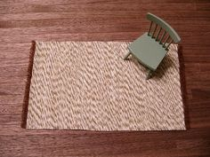 Miniature area rug - glue strands of variegated yarn to backing fabric which is fringed at the ends(test backing choice for fringing first - may need to be linen or part linen?) - sounds easy enough - see Finnish web-site referred too for a different example