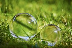 Two glass balls on the grass in the summer
