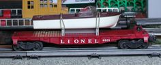Lionel postwar # 6801 Boat flatcar with a white-hull boat.