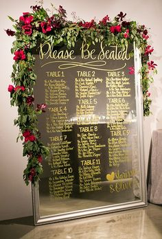 This mirrored seating chart is decked out with gold calligraphy and a lush garland with bright red blooms.
