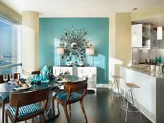 A turquoise accent wall with an oversized sunburst mirror is the focal point of this tropical, midcentury apartment.Design by Gacek Design Group