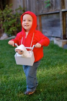 "Costume for Jake next year? ""Here's a picture of our son ... dressed as Elliot from the movie E.T. We made the ""milk crate"" from old cardboard and the handle bars from a few dry cleaning hangars and aluminum foil. The E.T. was found online. It's a bit old school but the other parents really seemed to enjoy it tonight."""