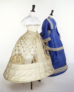 Blue wedding dress with white corset and underskirt. A three-piece wedding dress of blue watered silk and trimmed with lace. Its skirt is box-pleated at the sides and gathered at the back under the overskirt shaped like a continuation of the bodice. The corset is made of white ribbed cotton and has a glazed finished. The opening is placed at the center front with two busks of thick whalebone which close with three engraved metal keyhole and stud fastenings.