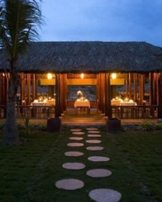 The jungle-clad grounds are studded with antiquated houses topped with shaggy palm thatch.