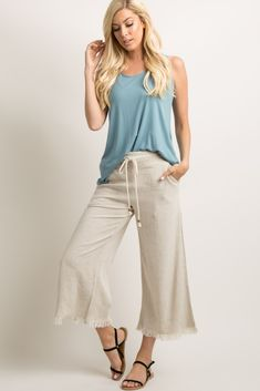 Solid hued, cropped linen pants featuring a braided beaded drawstring tie front, a fringe trim, and an elastic back. Additional details include a wide leg style, two side and two back pockets. Material has no stretch. This style was created to be worn before, during, and after pregnancy.