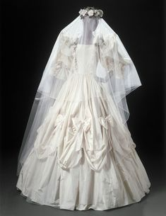 This dress was created by England's Elizabeth and David Emanuel for Liberty's 'Silk Cut' show in December 1979. With its festooned and trained crinoline-style skirt, and frills, bows, and fabric flowers, this romantic gown is a precursor of the Emanuels' design for Lady Diana Spencer's wedding dress in 1981. The Emanuels were inspired by Winterhalter's portraits of the 1860s...the same source that prompted Norman Hartnell to revive full- skirted styles for the Queen Mother in 1938.  Via V.