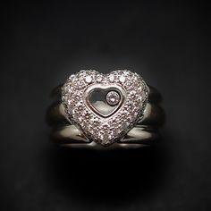 """à vendre : 3980€ Bague Chopard Happy Diamonds Or gris 18k Diamants. Taille 53. Modèle : """"Happy Diamonds"""" de 2002  Ref : 82/2017-20  sertie de petits diamants brillants  poids total : 1.50 ct G-VS dimensions du coeur : 15 mm x 13 mm  poids brut  : 15.60 gr  taille : 53  Bijou signé et numéroté  boite et facture d'origine mise à taille possible mais difficile Nous contacter avant d'acheter. Prix neuf en 2002 : 6510€"""