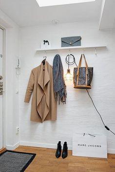 prateleira com ganchos para pendurar casaco, cachecol, bolsa no hall de entrada da casa, sacola amarc jacobs no chão