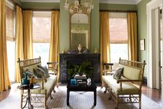 In the front parlor of Julia Reed and John Pearce's home in New Orleans, a 19th-century lacquer cocktail table is flanked by a pair of English Regency faux-bamboo benches upholstered in a Claremont fabric; the Italian-marble mantel is original to the house, and the gilt mirror and painted chairs are antique. The chandelier is from New Orleans Auction Galleries, the side table belonged to Reed's great-grandmother, and the walls are painted in Farrow & Ball's Sutcliffe Green.   - ELLEDecor.com