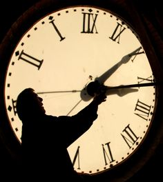 FILE - Custodian Ray Keen checks the time on a clock face after changing the time on the 97-year-old... - AP Photo/Charlie Riedel, File