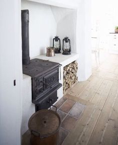 Simple and rustic kitchen design with a built in woodturning stove and rustic wooden floor