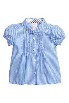 Blusa con pinzas pespunteadas: Blusa de rayas en tejido de algodón con cuello redondo. Botones y pinzas pespunteadas con bordado delante, y mangas cortas abullonadas con puños elásticos.
