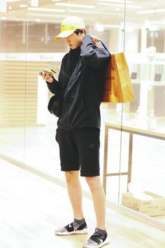 He looks like a boyfriend holding on to shopping bags while playing mobile games while waiting for his girlfriend I love him the most