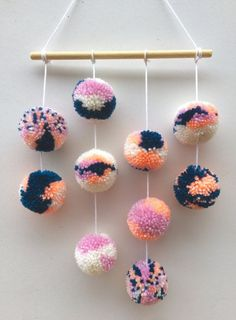 Pom pom wall hanging with 10 acrylic wool pom poms. Each pom pom is approximately 5cm in size. This would look great in a nursery, living room, bedroom or anywhere else you fancy. Each wall hanging is unique. The one pictured is available or you can specify your colour scheme at checkout and we will contact you to confirm shades. Bright Island goods come beautifully wrapped in tissue paper and twine. Due to the handmade nature the hanging should be handled with care to avoid losing wool a...