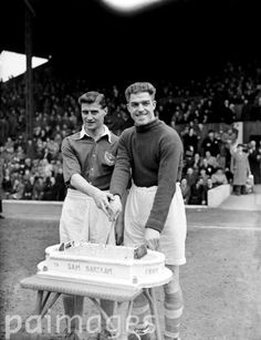 Portsmouth's Jimmy Dickinson helps Charlton Athletic goalkeeper Sam Bartram to cut the special cake awarded to him on the occasion of his 500th appearance for the club