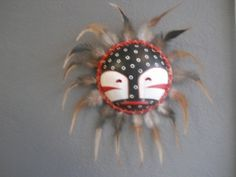 "Nalylgalan Mask, ""One Who Doesn't Know"" by Jerry Laktonen, Aleut Native from Kodiak Island, Alaska.  Dimensions with feathers 13"" x 13""."