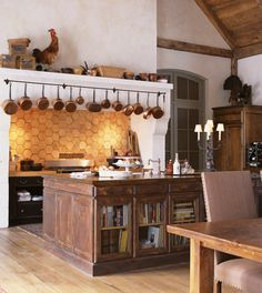 Grand Farmhouse Kitchen This warm and inviting cooking area beckons with a casual aesthetic and time-worn materials. Old is new again in this rustic kitchen, which offers a great backdrop for salvaged architectural items. Here, reclaimed hexagonal terracotta floor tiles from France create a striking backsplash with texture and patina.