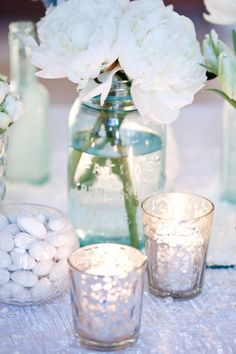 Mason jar centerpieces and mercury glass votives. A- blue jars with pictures, Starbucks jars with flower stem and small mason/votive with candle. I like different heights. Mason Jar Centerpieces, Mason Jars, Simple Centerpieces, Centrepieces, Wedding Reception, Our Wedding, Dream Wedding, Bali Wedding, Wedding 2015