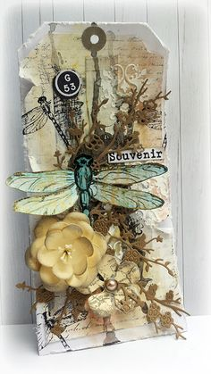 Tag by Susanne Rose: I used paper scraps for the background of my tag and adhered them with Gel Medium. After this was dry I covered it with a thin layer of gesso. I added more interest with some color, stamps and texture. The stamps are form Rubber Dance and Sheena Douglas.