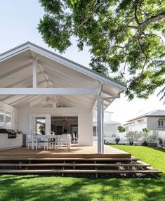 White high roof with wooden decking and steps.