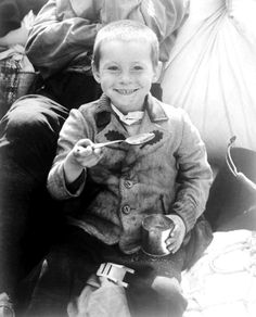 April 9, 1945: A young Polish boy enjoying his first meal (US Army rations) after American forces liberated his concentration camp. His sub-camp (of Buchenwald), Eisenach, required inmates to produce military equipment for BMW.