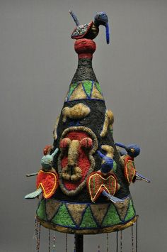 "Yoruba Crown - Nigeria                					  						                            						                					  					          	  This fully beaded Yoruba crown depicts birds, elephants, faces and geometric patterns. The crown stands 24"" tall. The veil beads are 25"" in length from the bottom of the crown. There is evidence of bead loss in the veil. The crown shows age and use with a darkened patina."