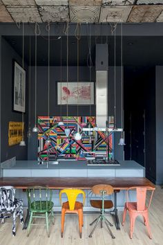 Cool loft kitchen (love the colorfull painting and chairs in a mostly gray area)