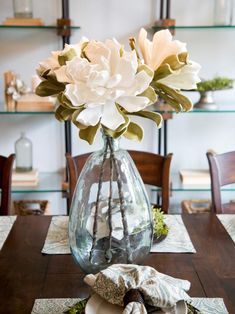 HGTV: The newly renovated dining room of the Gaspar home is adorned with a large glass vase holding elegant white flowers.