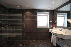 Black tiled ensuite floor and wall tiles the same Hotel Berg, Black Tiles, Restaurant, Wall Tiles, Bathroom Lighting, New Homes, Bathtub, Flooring, Mirror