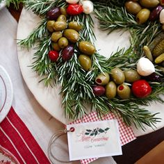 Talk about elevating a simplehors d'oeuvre to a whole new level – olives have never looked so good! The wreath is made of rosemary, and a variety of olives, tiny pickles, and mozzarella balls were arranged on top. The tag was made by scanning a ...