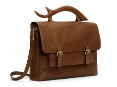 Inspired by the spirit of travel, this messenger bag is a reflection of your adventurous and original personality. The signature teak wood handle is complemented by a hand-stitched, full grain leather exterior and a sumptuous suede interior. Your belongings stay secure with 2 magnetic buttons, and the adjustable strap ensures all-day comfort in style while the front pocket leaves room for smaller accessories.