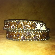 Floral tooled filagreed belt with cowhide background and tail painted white.  Briar brown antique stain and antique saskatoon stained flowers, fancy gun metal spots.