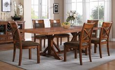 Gather friends, family, and guests around this delightful dining collection. Comfortable, stylish chairs feature smooth leather-like seat and back upholstery with nail head accents and an X-back design.  Available at Just Cabinets Furniture & More and online at JustCabinets.com
