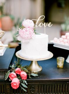 Elegant white wedding cake topped with a love sign: http://www.stylemepretty.com/california-weddings/san-juan-capistrano/2016/08/23/al-fresco-serra-plaza-wedding/ Photography: Kristina Adams - http://www.kristinaadamsphotography.com/