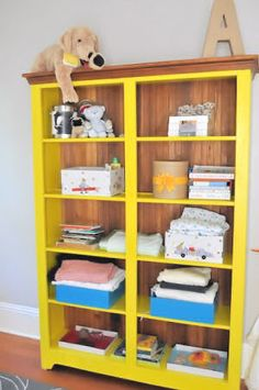 Bright yellow bookshelf painted with Confident Yellow Sherwin Williams paint with bins for clothes?