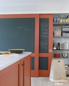 The closed-off prep kitchen of Moises Esquenazi and Bryan Graybill's Long Island home. They painted the sliding pantry doors with Benjamin Moore's roll-on chalkboard paint; the trim and cabinetry are Farrow & Ball's Blazer.
