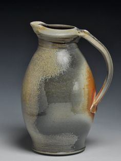 """Wood-fired Pitcher,#320:   This pitcher measures 9"""" tall. It went into the kiln with no glaze or decoration on the outside of the piece. During the three-day firing, using three cords of Chinese Elm fuel, the ash from the wood landed on the pitcher and created an all-natural-ash-glazed surface. You can rather imagine the flames sweeping around this piece, leaving their fire-marks. Elegant and understated at the same time."""