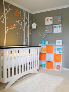 This crisp and modern crib looks stunning against the gray forest-inspired backdrop. The overall neutral color scheme allows pops of orange and turquoise to make a bold, energetic statement while still offering a soothing space for a baby to sleep.