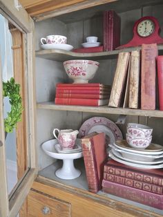 red vintage clock, books and transfer ware.