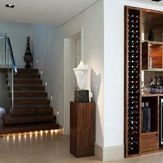 Escada em madeira com vaso, adega acoplada a estante e piso porcelanato. Parede e gesso branco com spot.
