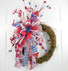 A versatile ready to use Terri Bow with Patriotic accents. The Terri Bow has six different ribbons and is mixed with glittery patriotic picks in red, white and blue. This is a reusable wreath accent y