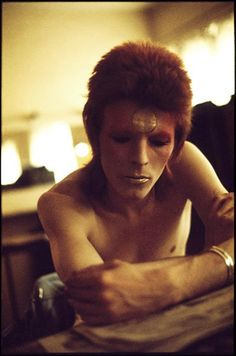 David in Ziggy makeup, taken backstage on the British tour before a show, 1973. Geoff says: 'This shot was taken before a show. David was reading a review and I sneaked this shot with a zoom lens. To this day, I find it remarkable how calm he is only moments before showtime.' Photograph: Geoff MacCormack/Rock Archive