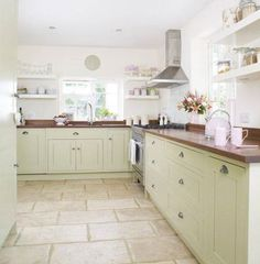 Wooden worktops complement this pastel-themed kitchen. Check out these other popular cabinet color options in this photo link.