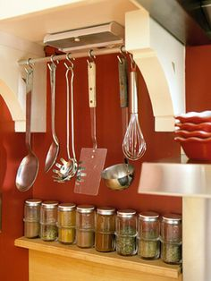 Install two end wooden brackets under a narrow kitchen cabinet, install a short curtain rod or other decorative bar, and hang kitchen utensils that don't fit in drawers or crowd those crocks on the counter top!