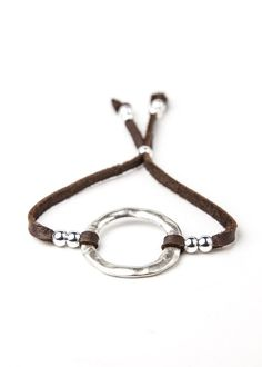 This gorgeous, unique bracelet is made with a hammered metal circle, strung on super soft leather lace with silver bead detailing. - Adjustable; sliding bead