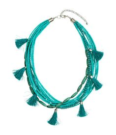 Short, multistrand necklace in metal with glass beads and tassels. Adjustable length, 20 - 23 1/2 in.