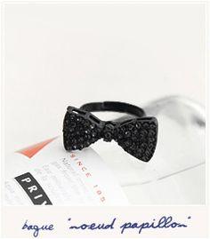 Bague noeud papillon serti de petites pierres noires scintillantes posé sur  un anneau en métal noir. 04c93ac3d29