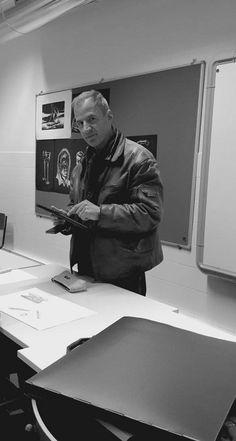 Esta foto foi tirada enquanto decoria uma aula de desenho. O senhor que se encontra nesta foto é o professor Pedro Tribuzi professor de desenho. Quanto ao cenário em si podemos constatar que é uma sala de aula e para os mais atentos podese ver desenhos afixados no quadro por de trás do professor. E em cima da mesa pode-mos constatar que se encontra um desenho e uma capa de alunos de artes.