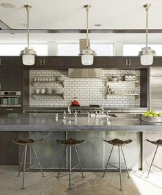 12 Concrete Interiors: The industrial modern kitchen is proving timeless, like this one in Santa Monica, California designed by Randy Weinstein. With its white subway tile paired with black grout, stainless steel finishes, vintage tractor seat stools, factory pendants, and a polished concrete floor, it's the epitome of the aesthetic.